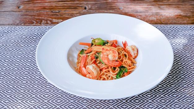 Die spaghetti würzigen garnelen in einem weißen teller auf der tischdecke.