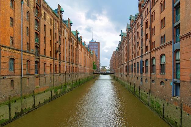 Die speicherstadt ist das wahrzeichen der stadt hamburg in deutschland. es ist der größte lagerbezirk der welt. rote backsteingebäude stehen auf holzpfahlfundamenten.