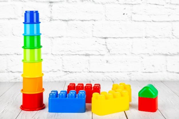 Die spielwaren der plastikkinder auf holztisch auf einem backsteinmauerhintergrund