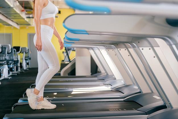 Die sportfrau, die auf tretmühle in der turnhalle läuft, hält sitz, brennt kalorien auf laufender maschine und trägt weiße sportkleidung und turnschuhe.
