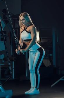 Die sportlerin in sportkleidung trainiert im fitnessstudio