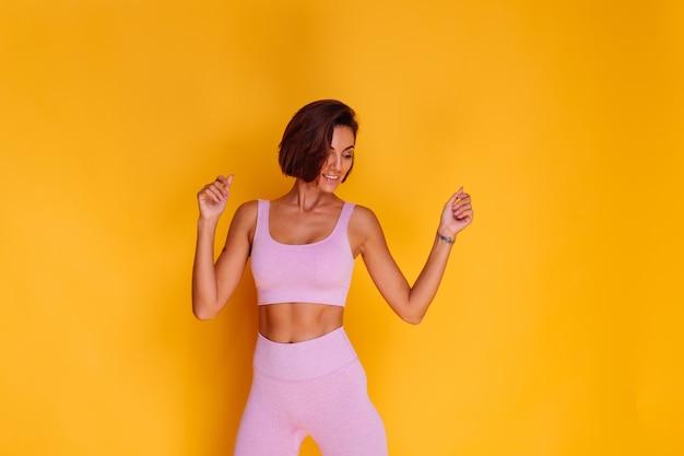 Die sportlerin steht auf einer gelben wand und zeigt ihre bauchmuskeln, ist mit den ergebnissen des fitnesstrainings und der ernährung zufrieden, hat einen glücklichen gesichtsausdruck, trägt ein sportoberteil und enge leggings