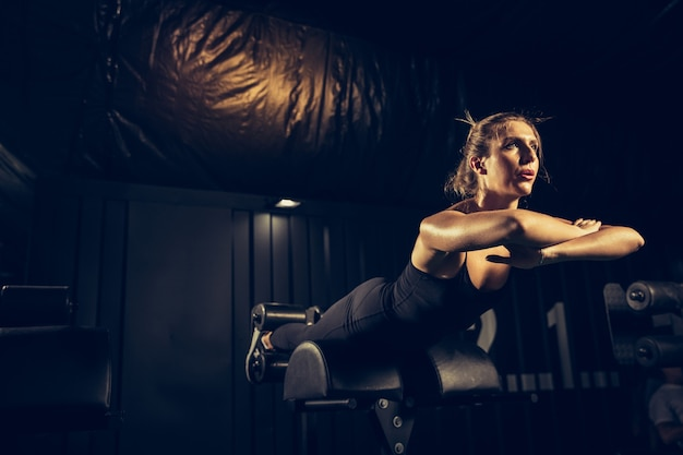 Die sportlerin trainiert hart in der turnhalle. fitness- und gesundes lebenskonzept.