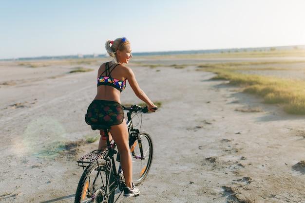 Die sportliche blonde frau in einem bunten anzug fährt an einem sonnigen sommertag in einer wüstengegend fahrrad. fitness-konzept. rückansicht