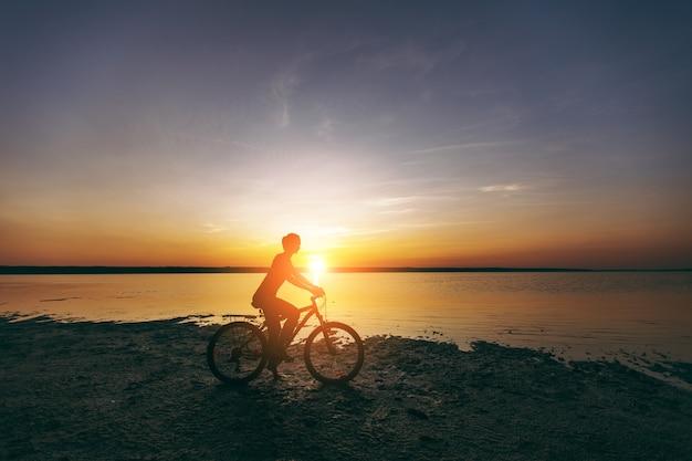 Die sportliche blonde frau in einem bunten anzug fährt an einem sonnigen sommertag in einer wüstengegend in der nähe des wassers fahrrad. fitness-konzept.
