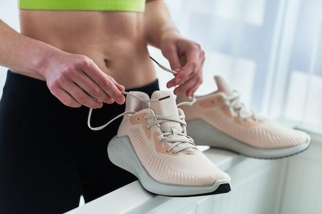Die sportliche fitnessfrau hält beige bequeme turnschuhe zum joggen und laufen. sport treiben und fit sein. sportler mit gesundem sportlichem lebensstil