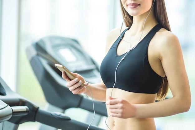 Die sportliche frau hält ein telefon im fitnessclub