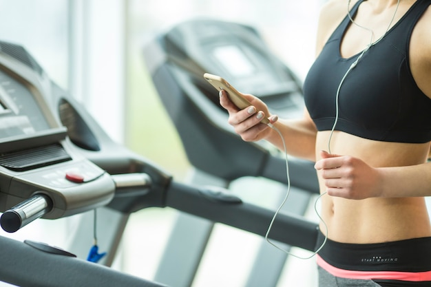 Die sportliche frau hält ein telefon im sportclub
