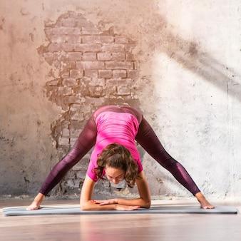 Die sportliche junge frau, die yogaübungen auf übungsmatte tut