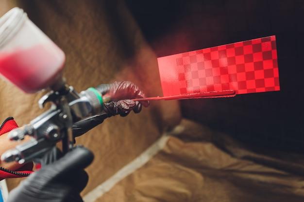 Die spritzpistole in den händen des meisters ist auf eine testplatte gerichtet und sprüht farbe in eine tönungshaube.