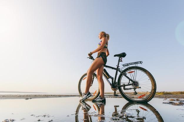 Die starke blonde frau in einem bunten anzug steht neben einem fahrrad in einem wüstengebiet am wasser. fitness-konzept.