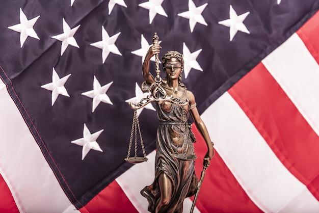 Die statue der gerechtigkeit themis oder iustitia die göttin der gerechtigkeit mit verbundenen augen gegen eine flagge der un...