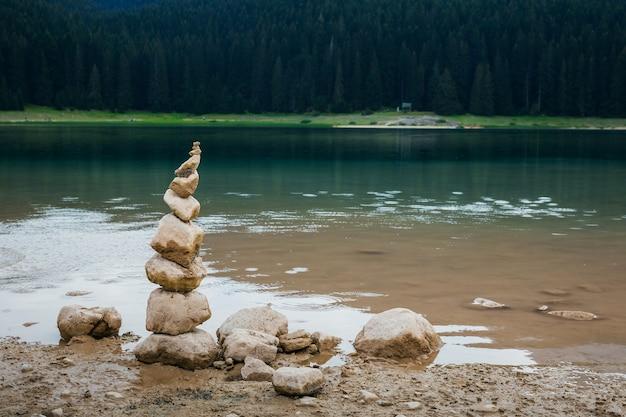 Die steinpyramide befindet sich am ufer eines schwarzen sees in montenegro