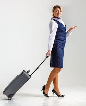 Die stewardess geht und rollt ihren koffer.