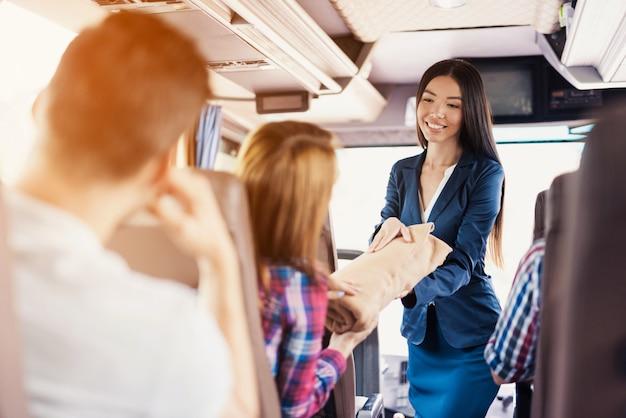 Die stewardess im bus gibt der frau eine warme decke.