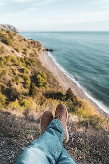 Die stiefel und beine des mannes mit der küste im hintergrund. konzept der erkundung und abenteuer