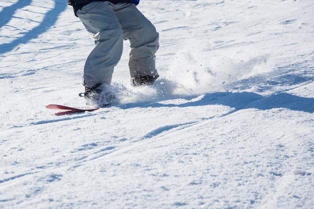 Die stiefel und der snowboard freerider der männer im gebirgswintersport, lebensstil der freizeit im freien