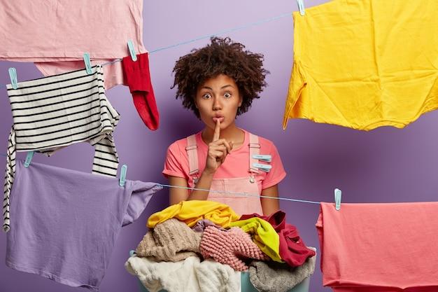 Die stille, dunkelhäutige hausfrau hängt saubere wäsche an die wäscheleine, hält den vorderfinger über die lippen, hat einen übermütigen look, ist damit beschäftigt, kleidung zu putzen, hat wäscheklammern an overalls und verbreitet gerüchte über nachbarn