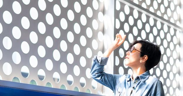Die stilvolle asiatische frau mittleren alters, die eine sonnenbrille mit 100% uv-lichtschutz trägt, steht innen und hebt die hand, um helle blendung und sonnenlicht von außen abzuhalten und eine überbelichtung mit ultravioletten strahlen zu vermeiden