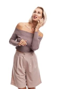 Die stilvolle junge blonde frau im rosa anzug spricht am telefon und schaut verträumt zur seite. auf weißer wand isoliert.