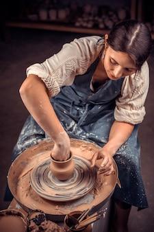 Die stilvolle meisterin demonstriert den prozess der herstellung von keramikgeschirr mit der alten technologie. keramikgeschirr zubereiten.