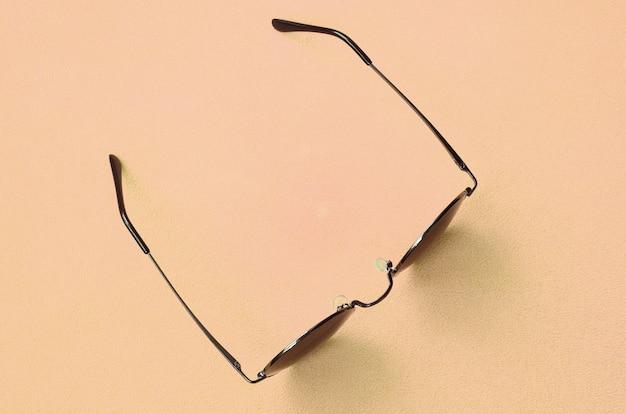 Die stilvolle schwarze sonnenbrille mit runder brille liegt auf einer decke aus weichem und flauschigem hellorangenem fleece.