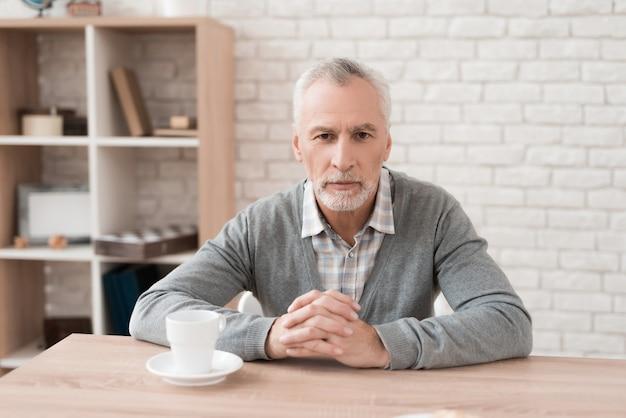 Die stirn runzelnder bärtiger alter mann sitzt bei tisch zu hause.
