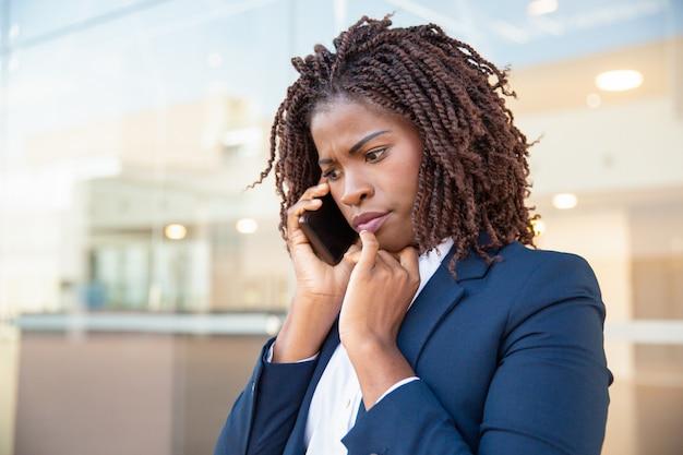 Die stirn runzelnder betroffener manager, der über mobiltelefon spricht