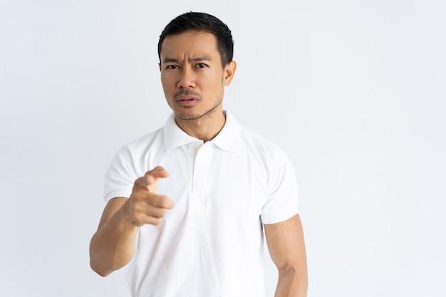Die stirn runzelnder junger mann, der finger auf kamera zeigt