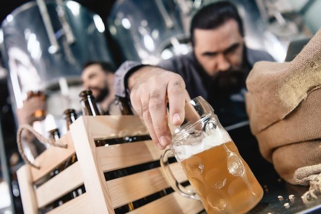 Die stirn runzelnder mann, der bier in der becher-mikrobrauerei kontrolliert.