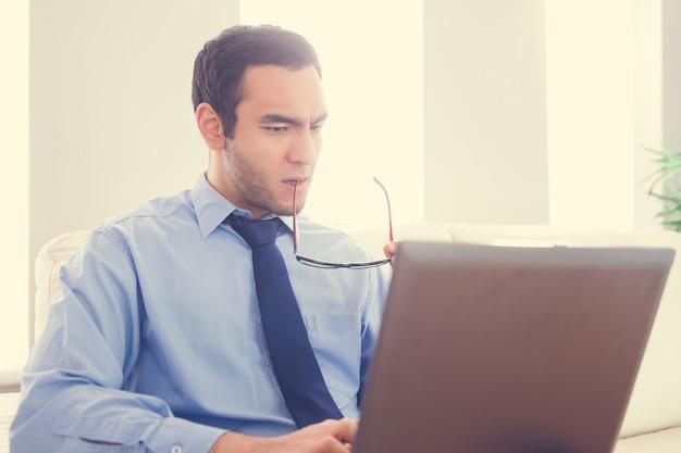 Die stirn runzelnder mann, der seine brillen beißt und einen laptop verwendet