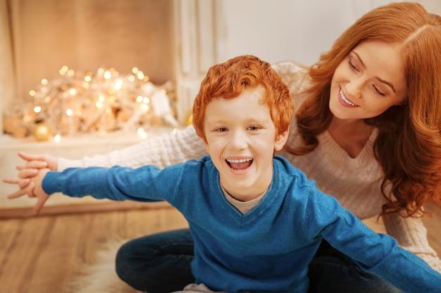 Die strahlende jungenhaltung ist weit geöffnet, während sie sich während einer lustigen weihnachtszeit mit der familie aufregt.