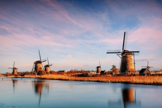 Die straße, die vom kanal zu den holländischen windmühlen führt