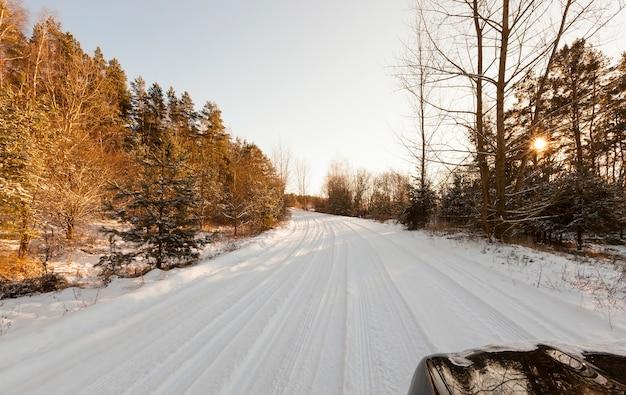 Die straße im wald ist mit schnee und geriffelten spurrillen bedeckt. foto im winter, rechts ist ein auto, von dem aus die motorhaube sichtbar ist.