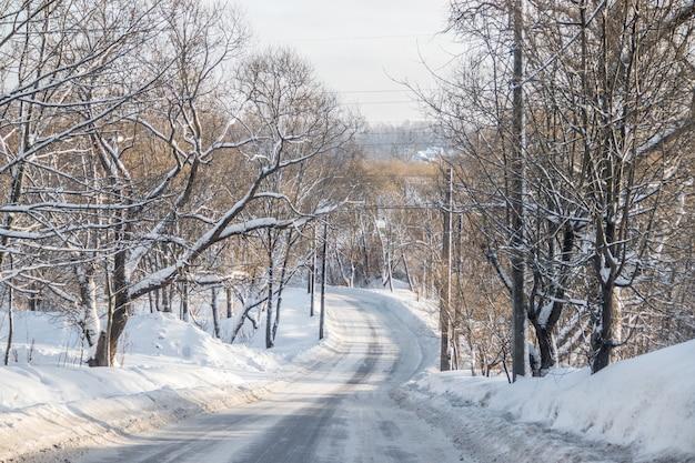 Die straße im winterwald. schneebild. äste von bäumen im schnee hängen über der straße.