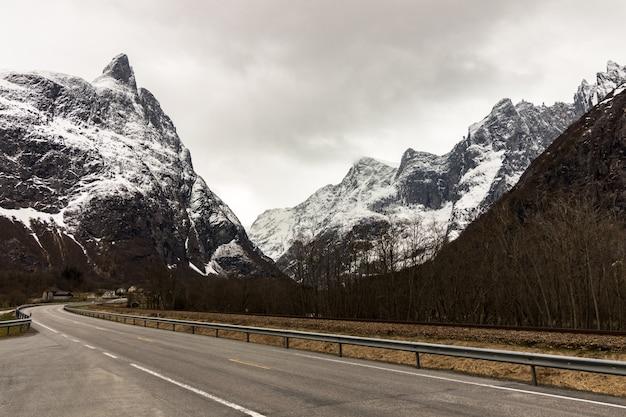 Die straße in andalsnes mit den majestätischen berggipfeln des bergmassivs trolltindene