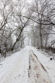Die straße ist nach kälte und frost gefährlich und rutschig, eine straße, die in der wintersaison mit schnee bedeckt ist