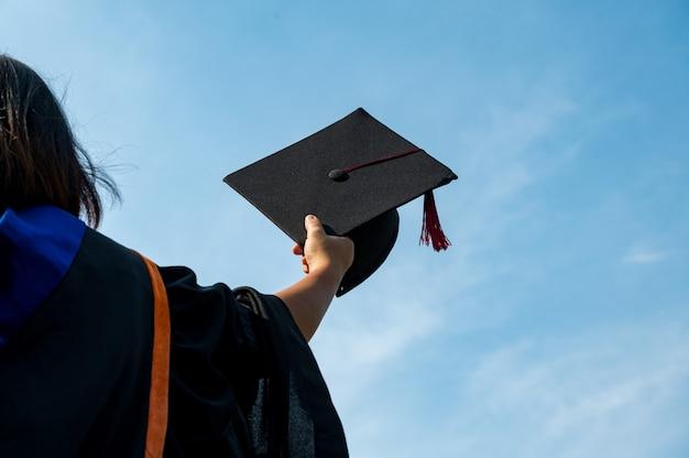 Die studenten halten einen schuss abschlusskappe an der hand in einem hellen himmel