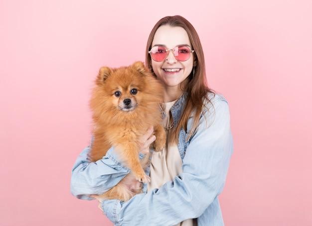 Die studioaufnahme des weiblichen modells hält das flauschige haustier dicht am gesicht, lächelt vor glück und posiert vor dem rosa hintergrund.
