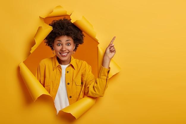 Die studioaufnahme einer positiven afroamerikanerin zeigt mit dem finger auf den kopierraum oben, ist von guten informationen begeistert, lächelt angenehm, trägt eine gelbe jacke und steht in einem zerrissenen papierloch.
