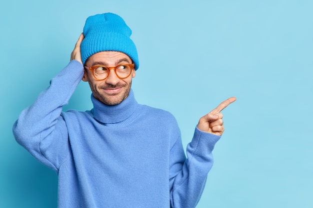 Die studioaufnahme eines fröhlichen männlichen teenagers in modischer kleidung sieht interessiert aus und zeigt auf den kopierraum