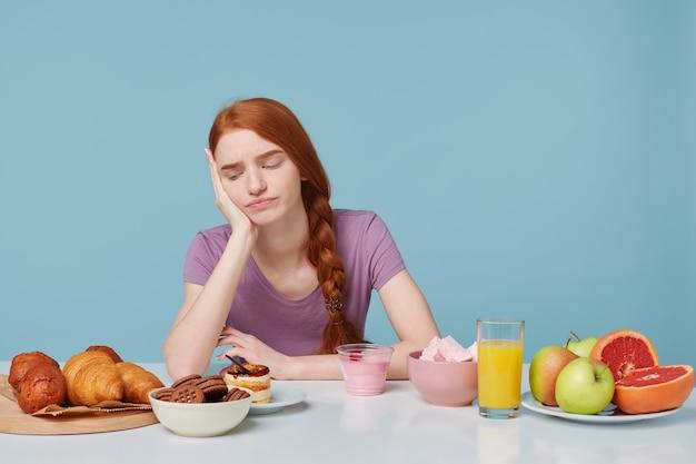 Die studioaufnahme eines rothaarigen mädchens, das mit unzufriedener traurigkeit auf backwaren schaut, denkt darüber nach, was zu essen ist