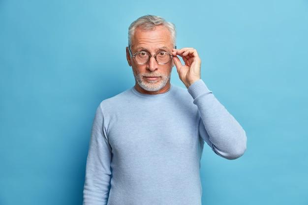 Die studioaufnahme eines überraschten reifen mannes sieht mit staunen aus und trägt eine optische brille. der lässige pullover hört schockierende nachrichten, die über der blauen wand isoliert sind und von einem fantastischen ereignis beeindruckt sind