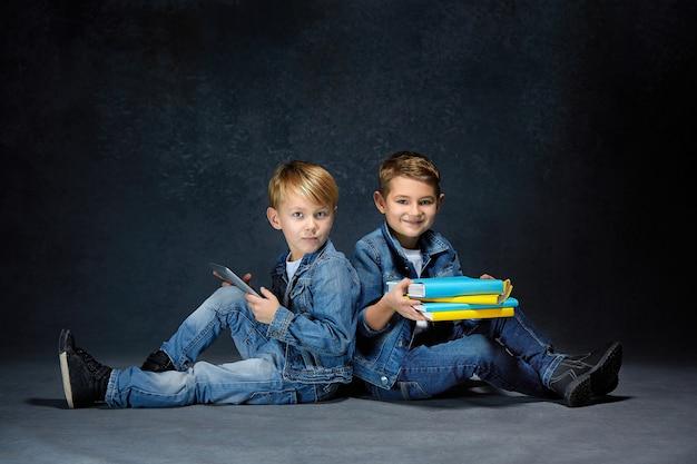 Die studioaufnahme von kindern mit büchern und tablette