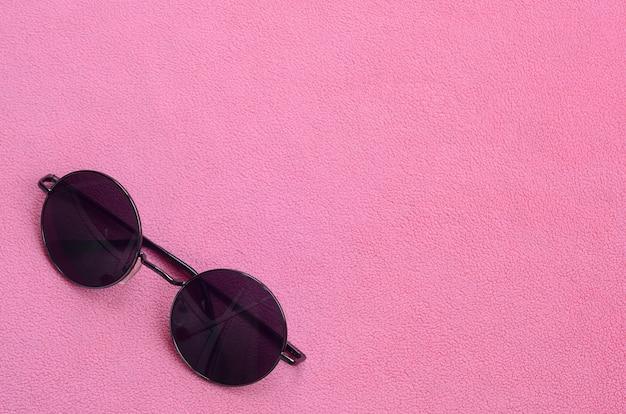 Die stylische schwarze sonnenbrille mit runder brille liegt auf einer decke aus weichem und flauschigem hellrosa fleece.