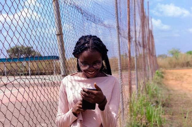 Die süße afrikanische dame, die im freien steht, lächelt, während sie ihr handy bedient
