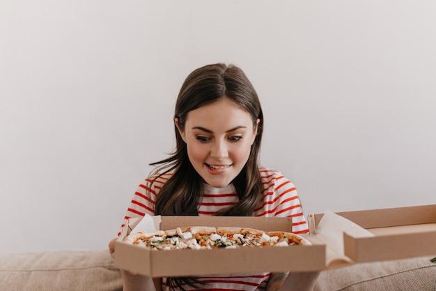Die süße brünette beißt sich auf die lippe, während sie sich die leckere pizza ansieht