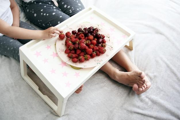 Die süße mutter und ihre tochter sitzen auf dem bett und essen erdbeeren und kirschen