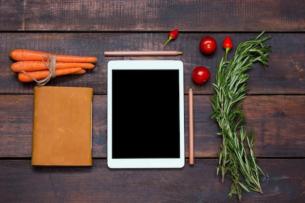 Die tablette, das notizbuch, der frische bittere und gemüsepaprika auf holztischhintergrund