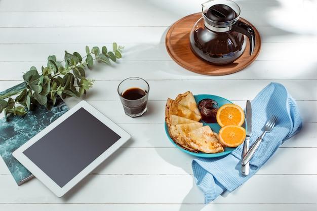 Die tablette und pfannkuchen mit saft. gesundes frühstück